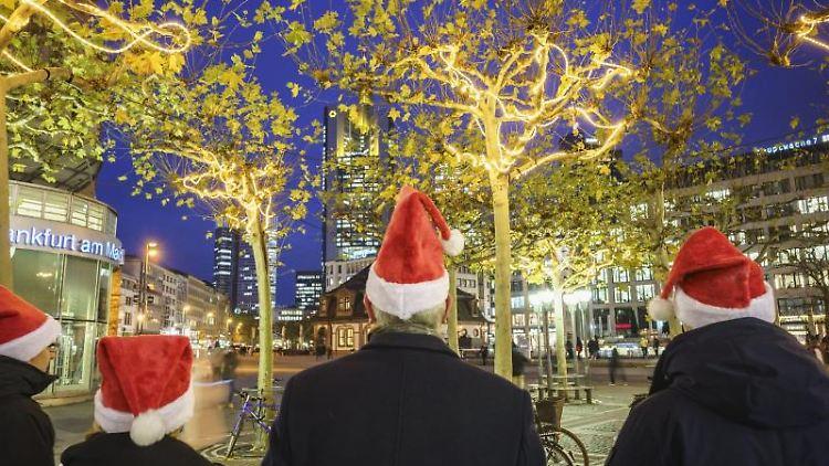 Menschen vor der Weihnachtsbeleuchtung auf der Frankfurter Zeil. Foto: Frank Rumpenhorst/dpa