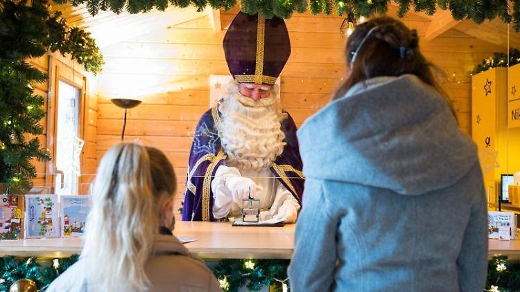 Der Nikolaus stempelt in der neuen Nikolaushütte einen Brief von zwei Mädchen ab. Foto: Oliver Dietze/dpa