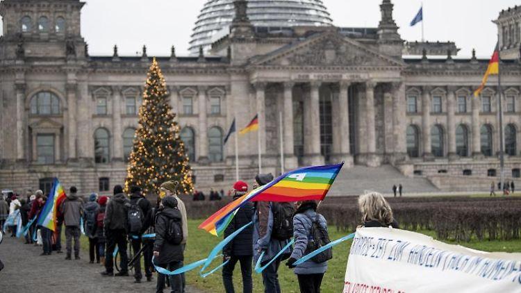 Teilnehmer bilden eine Menschenkette beim bundesweiten Aktionstag gegen Aufrüstung. Foto: Fabian Sommer/dpa