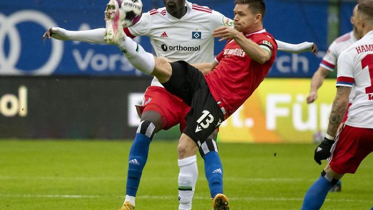 Hamburgs Amadou Onana (l) und Hannovers Dominik Kaiser kämpfen um den Ball. Foto: Axel Heimken/dpa