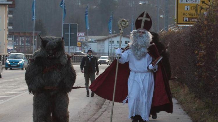 Ein Krampus und ein Nikolaus laufen durch die Stadt. Foto: Kilian Pfeiffer/dpa