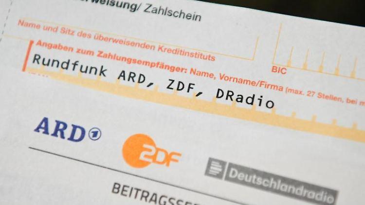 Auf einem Tisch liegt ein Anschreiben und Überweisungsträger für die Rundfunkgebühren. Foto: Nicolas Armer/dpa/Archiv