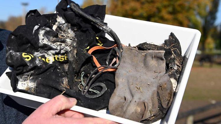 Storchenbetreuer Eisenbarth zeigt Unrat, den er in einem Storchennest gefunden hat. Foto: Uli Deck/dpa