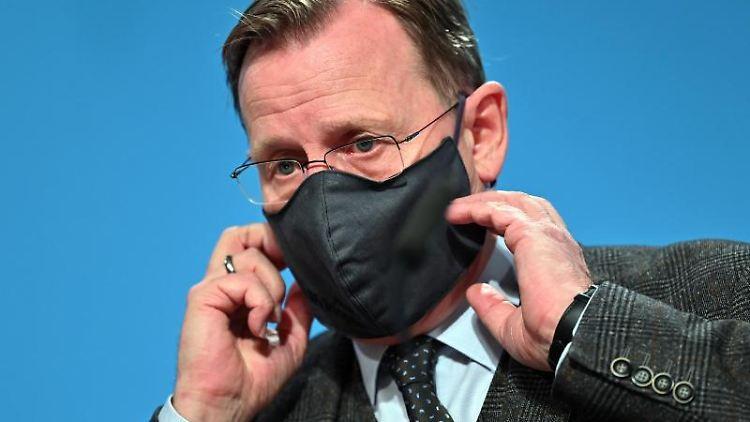 Bodo Ramelow (Die Linke), Ministerpräsident von Thüringen, setzt seine Mund-Nasen-Bedeckung ab. Foto: Martin Schutt/dpa-Zentralbild/dpa
