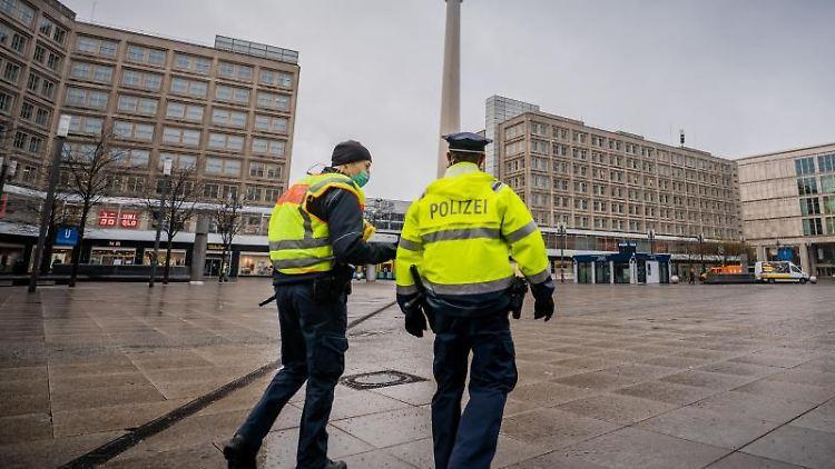 Polizisten gehen über den ansonsten weitgehend leeren Alexanderplatz in der Hauptstadt. Foto: Michael Kappeler/dpa/Aktuell