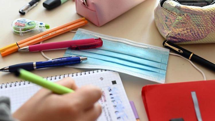 In einer Schule liegt während einer Unterrichtsstund ein Mund-Nasen-Schutz auf dem Tisch. Foto: Uli Deck/dpa/Symbolbild