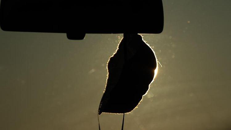 Eine FFP2-Maske hängt vor der aufgehenden Sonne in einem Auto. Foto: Sebastian Gollnow/dpa/Symbolbild