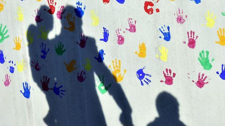 Ein Mann mit einem Kind auf dem Arm und einem an der Hand wirft einen Schatten auf eine mit bunten Handabdrücken bemalte Wand. Foto: Peter Kneffel/dpa/Symbolbild