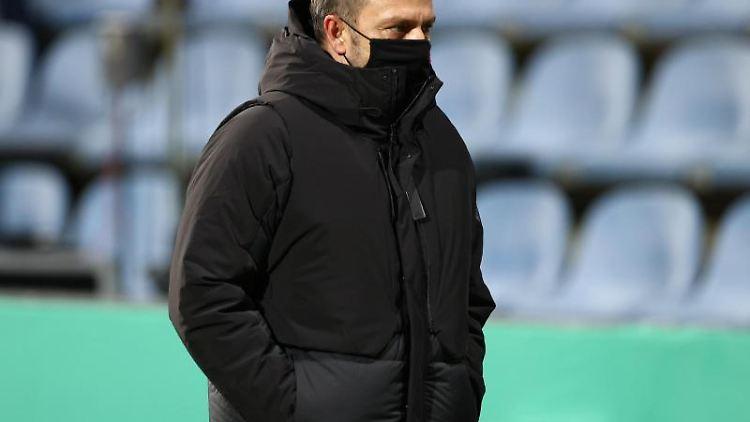 Trainer Hansi Flick von München steht vor einem Spiel auf dem Spielfeld. Foto: Christian Charisius/dpa