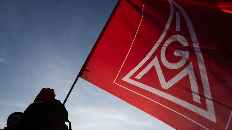 EinDemonstrant hält eine IG Metall-Flagge in der Hand. Foto: Marijan Murat/dpa/Symbolbild