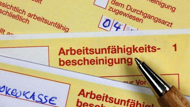 Krankmeldungen liegen auf einem Schreibtisch (gestellte Szene). Foto: Jens Büttner/dpa-Zentralbild/dpa/Archivbild