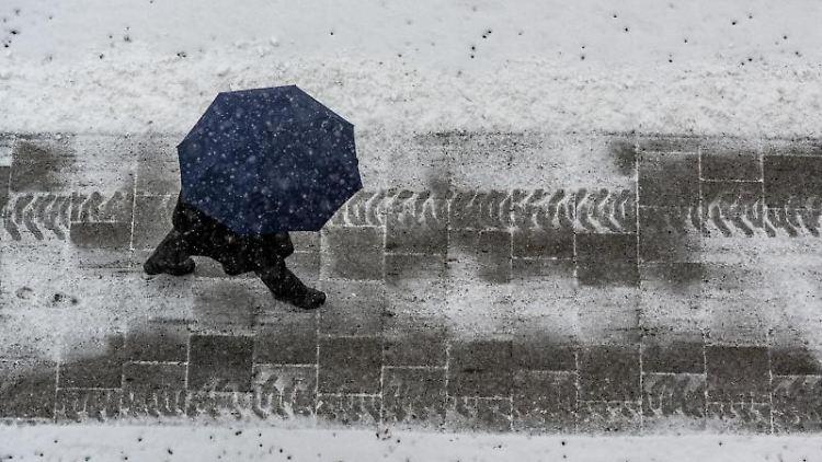 Ein Fußgänger mit Regenschirm ist auf einer mit Schnee bedeckten Straße unterwegs. Foto: Armin Weigel/dpa/Archivbild