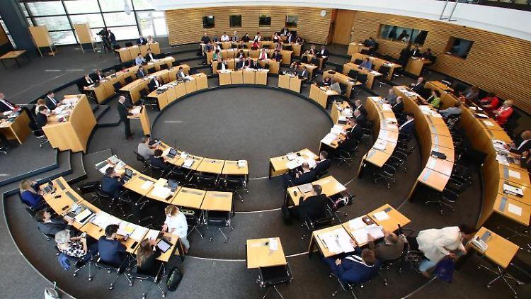 Abgeordnete sitzen bei der Sitzung des Thüringer Landtages im Plenarsaal. Foto: Bodo Schackow/dpa-Zentralbild/dpa