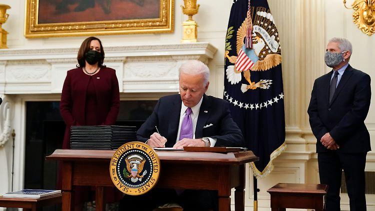 US-Präsident Joe Biden unterzeichnet Verordnungen für eine nationale Strategie im Kampf gegen die Corona-Pandemie. Mit vor Ort sind US-Vizepräsidentin Kamala Harris und Immunologe Anthony Fauci.