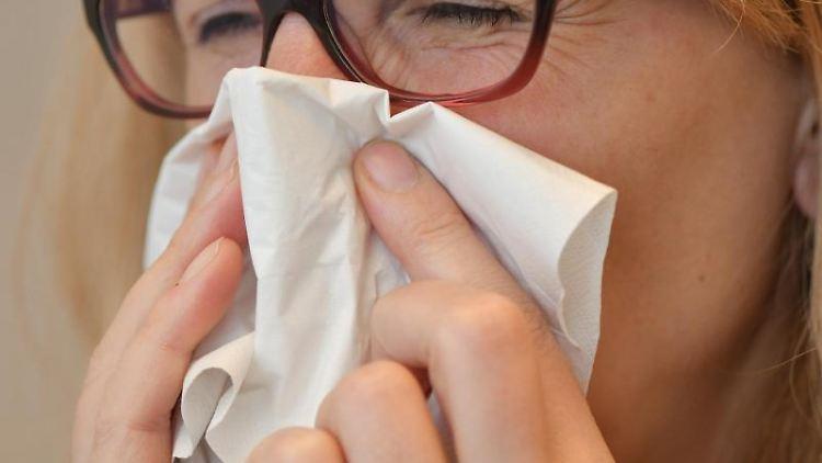 Eine Frau schnäuzt sich die Nase mit einem Papiertaschentuch. Foto: Patrick Pleul/dpa-Zentralbild/dpa/Illustration