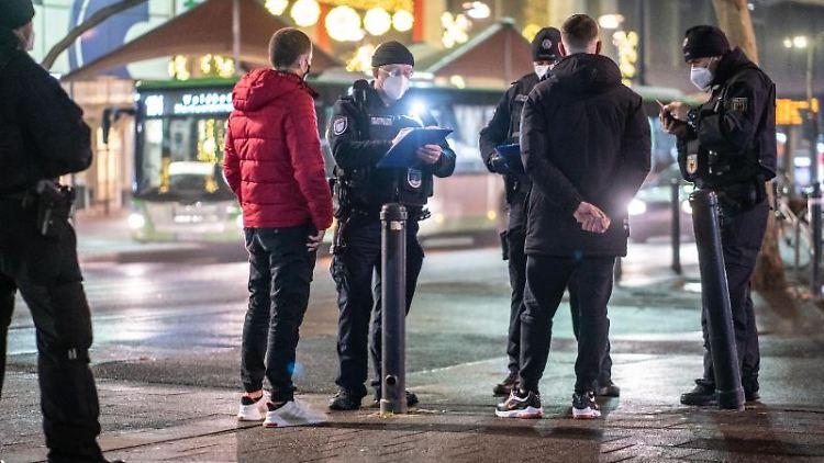 Polizeibeamte nehmen nachts in Offenbach die Personalien von zwei jungen Männern auf. Foto: Frank Rumpenhorst/dpa/Archivbild