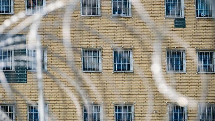 Blick durch den Stacheldrahtzaun auf die Fenster einerJustizvollzugsanstalt. Foto: Peter Steffen/dpa/Symbolbild