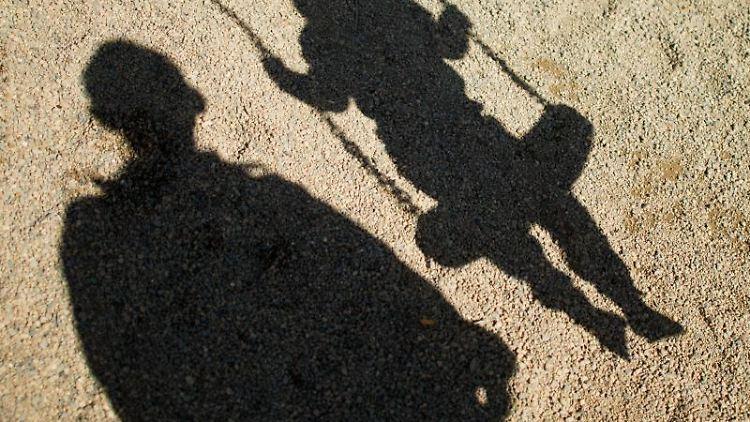 Der Schatten von einem Mann und einem schaukelnden Kind fallen auf den Sand auf einem Spielplatz. Foto: Julian Stratenschulte/dpa/Illustration