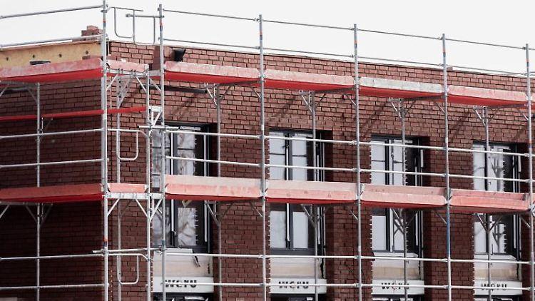 Ein Neubau steht eingerüstet auf einem Baufeld. Foto: Rolf Vennenbernd/dpa/Symbolbild