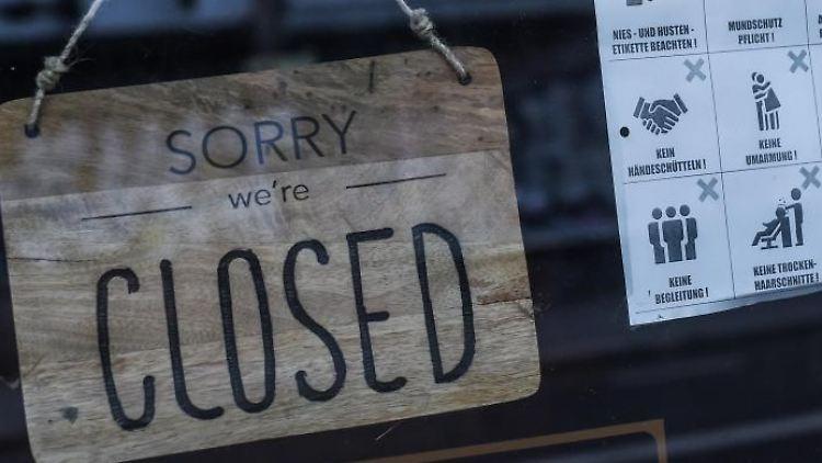 """An einem Friseur in Berlin hängt ein Schild mit der Aufschrift """"Sorry we're closed"""". Foto: Kira Hofmann/dpa-Zentralbild/dpa"""