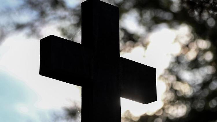 Ein Kreuz im Gegenlicht auf einem Friedhof. Foto: Patrick Pleul/dpa-Zentralbild/ZB/Symbolbild