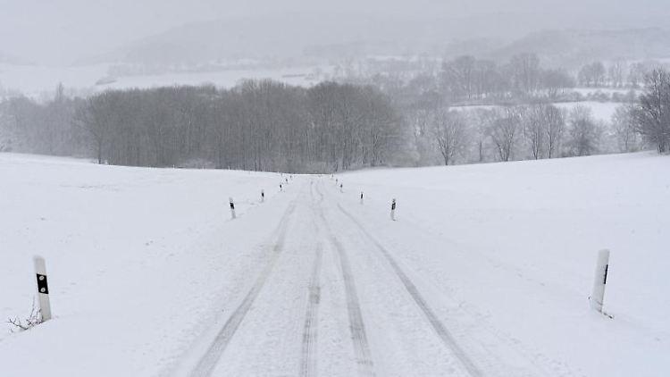Eine Fahrspur zieht sich durch eine verschneite Straße im Erzgebirge. Foto: Robert Michael/dpa-Zentralbild/dpa
