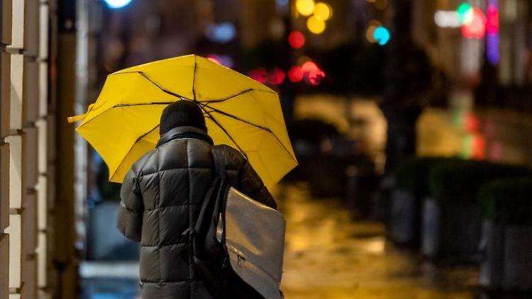 Ein Passant geht bei Regen durch die Stadt. Foto: Peter Kneffel/dpa/Symbolbild