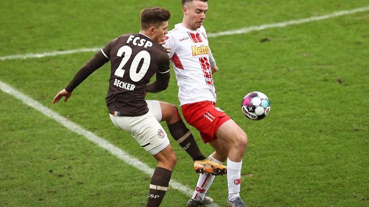 St. Paulis Fin Ole Becker und Regensburgs Max Besuschkow (l-r.) im Zweikampf um den Ball. Foto: Christian Charisius/dpa