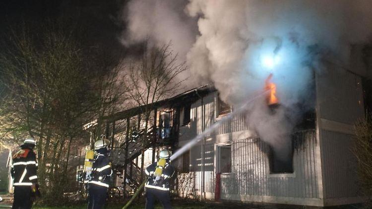 Mitarbeiter der Feuerwehr löschen in Hamburg-Billstedt den Brand in der Unterkunft für Geflüchtete. Foto: Daniel Bockwoldt/dpa