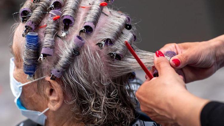 Einer Kundin werden in einem Friseursalon die Haare frisiert. Foto: Jens Büttner/dpa-Zentralbild/dpa/Symbolbild
