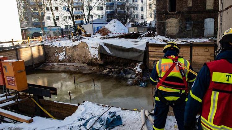 Einsatzkräfte des Technischen Hilfswerks (THW) stehen an einer Baugrube neben Wohnhäusern in Köpenick. Foto: Paul Zinken/dpa