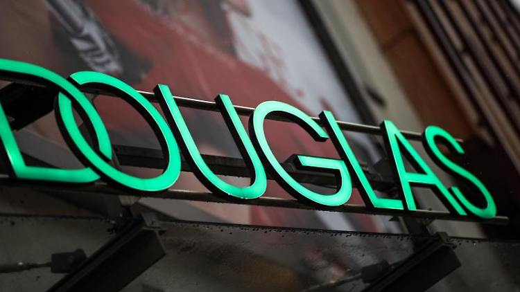 Das Logo der Parfümeriekette Douglas steht über dem Eingangsbereich einer Filiale. Foto: Daniel Karmann/dpa