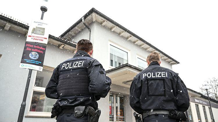 Zwei Polizisten sichern nach der Tötung einer 62-Jährigen das Bahnhofsgelände.