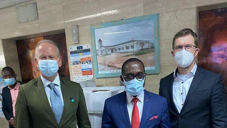Ingo Herbert, Botschafter aus Deutschland, Eugène Aka Aouélé, Gesundheitsminister der Elfenbeinküste, und Frank Theeg, Geschäftsführer des Chemnitzer Unternehmens Authentic Network, stehen zusammen. Foto: -/Authentic Network/dpa/Handout