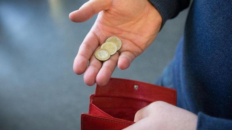 Münzen im Wert von fünf Euro werden über ein rotes Portemonnaie gehalten. Foto: Friso Gentsch/dpa/Archivbild