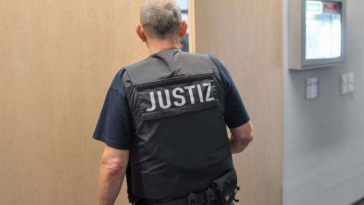 Ein Justizmitarbeiter schließt einen Verhandlungssaal auf. Foto: Patrick Pleul/zb/dpa/Symbolbild