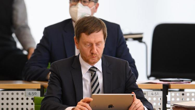 Michael Kretschmer (CDU) schaut auf sein Tablet. Foto: Robert Michael/dpa-Zentralbild/dpa/Archivbild
