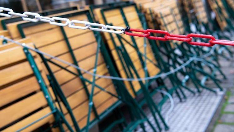 Zusammengeklappte Stühle und Tische stehen im Außenbereich einer geschlossenen Gaststätte. Foto: Sven Hoppe/dpa/Symbolbild