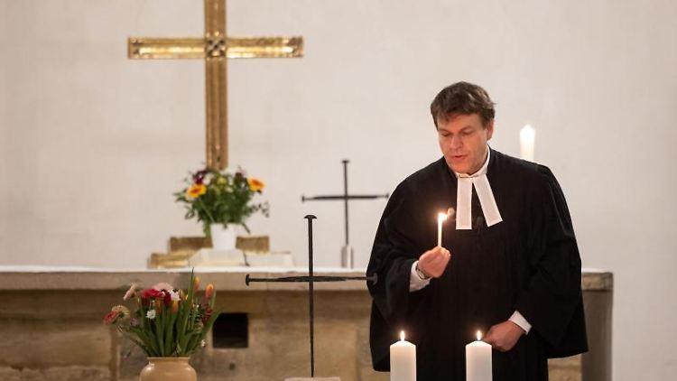 Pfarrer Bernd Prigge entzündet Kerzen für die Opfer des Bombenangriffs auf das Augustinerkloster. Foto: Michael Reichel/dpa-Zentralbild/dpa