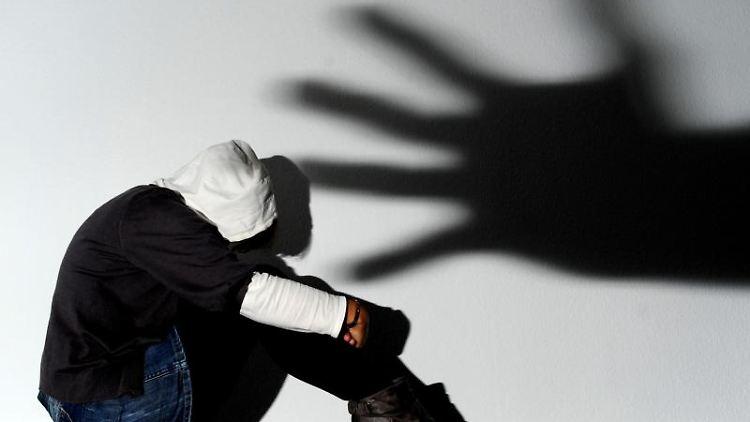 Ein Mädchen sitzt vor einer Wand, auf der der Schatten einer Hand groß zu sehen ist. Foto: picture alliance/dpa/Symbolbild