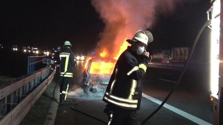 Einsatzkräfte löschen auf der Autobahn 1 einen in Vollbrand stehenden Kleinwagen. Foto: David Poggemann/Nord-West-Media/dpa