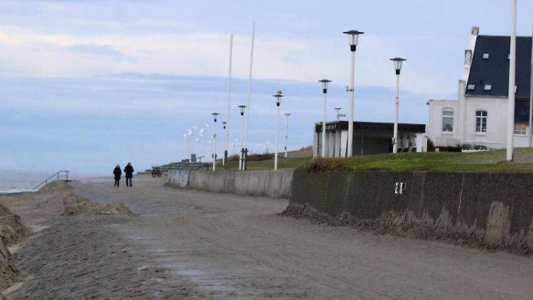 Spaziergänger sind am Weststrand der Nordsee-Insel unterwegs. Foto: Volker Bartels/dpa/Archivbild