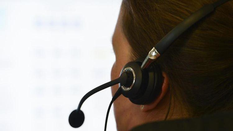 Eine Frau mit einem Headset sitzt an einem Arbeitsplatz. Foto: picture alliance / dpa/Archivbild