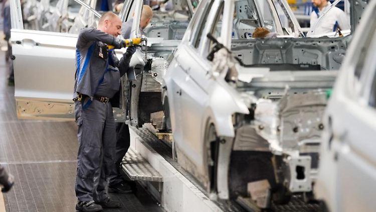 Mitarbeiter montieren Kotflügel an eine Autokarosserie. Foto: Julian Stratenschulte/dpa/Archivbild