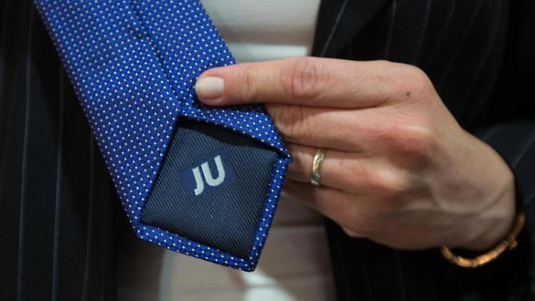 Eine Frau zeigt eine Krawatte, auf deren Rückseite das Logo der Jungen Union eingestickt ist. Foto: picture alliance/dpa/Archivbild