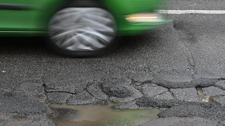 Ein Auto fährt über eine Straße mit Schlaglöchern. Foto: Patrick Pleul/dpa-Zentralbild/ZB/Archivbild