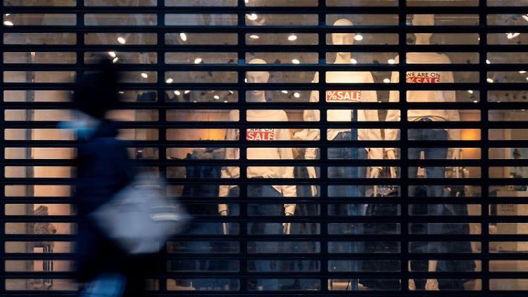Eine Passantin geht auf einer Einkaufspassage an einem geschlossenen Bekleidungsgeschäft vorbei. Foto: Marijan Murat/dpa/Symbolbild