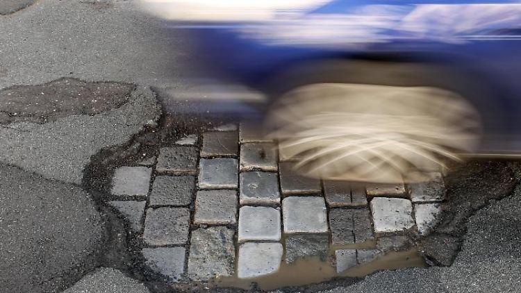 Ein Auto fährt über eine Straße mit Schlaglöchern. Foto: Jan Woitas/dpa-Zentralbild/dpa/Archivbild