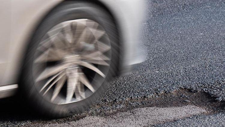 Ein Auto fährt über ein Schlagloch. Foto: Julian Stratenschulte/dpa/Symbolbild