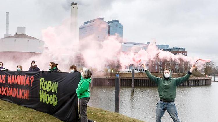 Aktivisten der Umweltschutzorganisation Robin Wood demonstrieren vor dem Kraftwerk Tiefstack hinter einem Transparent mit der Aufschrift